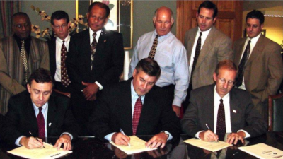 Louisiana Nursing Home Association. Three men in suites at a desk in the foreground, signing documents. A row of people standing behind them.