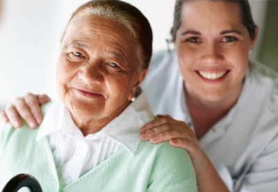 Louisiana Nursing Home Association. An elderly woman on the left with a younger woman behind her with her hands on her shoulders.