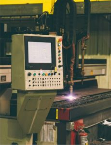 SMICO. A photo of a piece of equipment in progress with a bright light where it is making contact with a metal. On the left a control panel.
