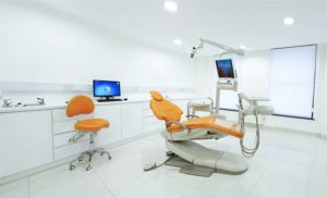 A clean well lit dental room all white. A white counter along the left wall with a computer monitor and chair next to it. In the center of the room is a dental chair with another monitor on it.