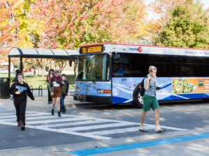 Grand Valley State University students cross the street with a bus stopped at a bus station behind.