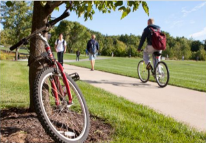 Grand Valley State University students walking and riding on a pedestrian path with a bike next to a tree in the foreground.