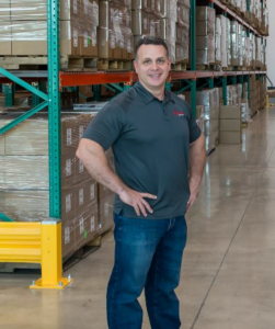 Jay Cohen, CEO of IQ Formulations standing in a warehouse with a shelving unit and product behind him.