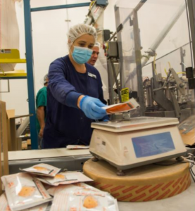 IQ Formulations employees processing and weighing product on a scale with a pile of bags next to the scale in the foreground.