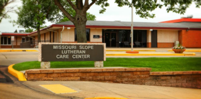 Missouri Slope Lutheran Care Center. Front of the care center building in the background, with their building sign in the foreground by the road.