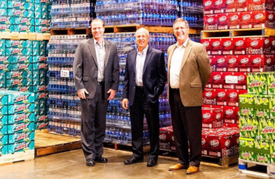 Walton Beverage Company. Three men in suits standing in a warehouse in front of pallets of beverages.