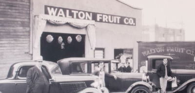 Walton Beverage Company. Old black and white photo of the Walton Fruit Company building with men standing next to vehicles out front.