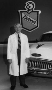 Black and white photo of a man with a white coat standing in front of a Zeibart sign with a car on the right.