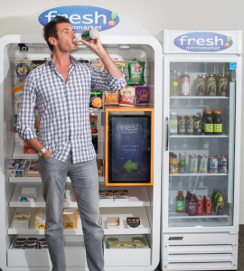 Fresh Healthy Vending. Two vending machines side by side with fresh! at the top of each. A man standing in front of the one on the left drinking a drink.