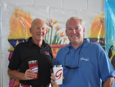 Gordy's Lakefront Marine, two older employees stopping for a photo holding up Gordy's cups.