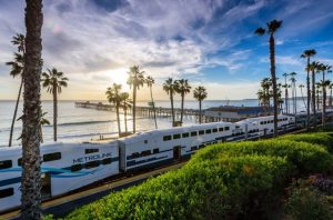 metrolink train with palm trees and sunset background