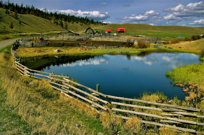 Cariboo Regional District. A ranch view overlooking a pond surrounded by wood fence with a building in the background and hills to the sides.