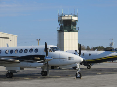 Two airplanes with the control tower behind them at Coastal Carolina Regional Airport.