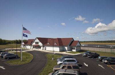 Knox County Regional Airport building with cars parked out front and small planes behind.