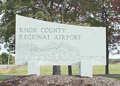 Knox County Regional Airport sign along the road with trees behind.