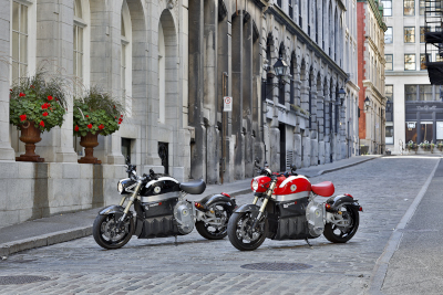 Two Sora motorcycles parked on a brick paved street with stone buildings behind them on the left.