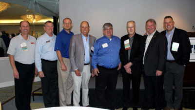 A group of men with the metal construction association standing in a row for a photo.