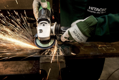 A person wearing gloves, using a grinder tool on metal, sparks flying.