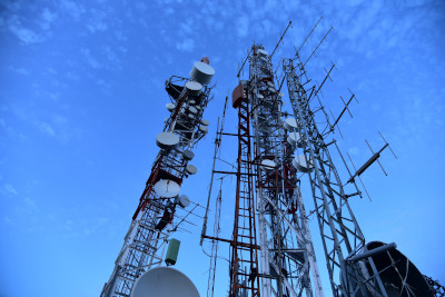 A few metal towers with dishes and other antennas and equipment mounted on them reaching to the blue sky.