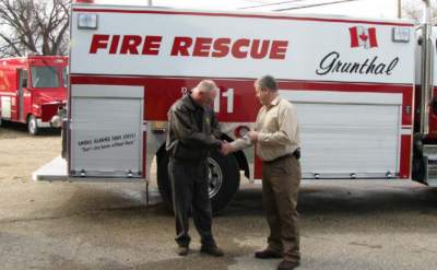 Rural Municipality of Hanover. Two men shaking hands in front of a Fire Truck.