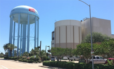 A large water tower on the left with a building on the right.