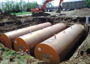 3 Steel tanks at a construction site in a dug up space in the ground.