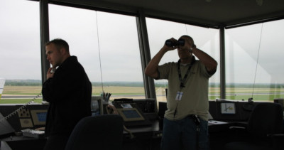 Two men working in a control tower at Stillwater Regional Airport.