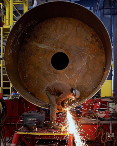 A worker using a tool, with sparks flying, on a large round metal object.