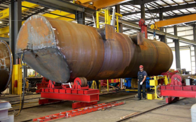 Large metal tank hanging in a production area being worked on.