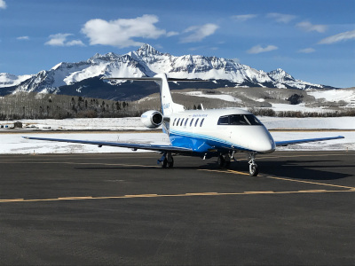 An airplane at Telluride Regional Airport, on the tarmac with a mountain and blue sky behind.